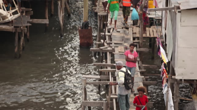 people on bridge through water village papua new guinea is an island located in oceania there are around 850 languages spoken on the island and there... - oceania stock videos and b-roll footage