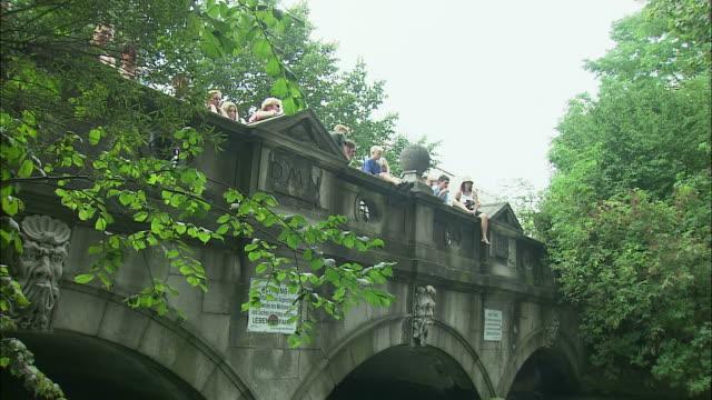 MS TD People on bridge watching surfers on Eisbach river in Englischer Garten (English Garden), Munich, Bavaria, Germany