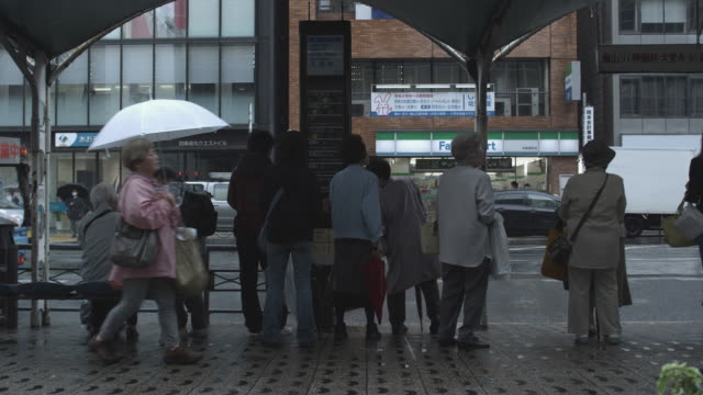ms people on bus stop in rain, kyoto, japan - bushaltestelle stock-videos und b-roll-filmmaterial