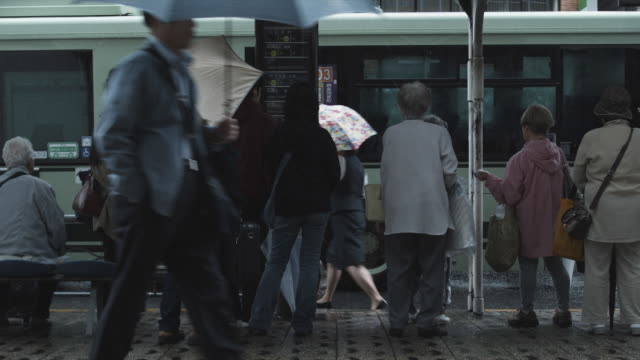 ms people on bus stop in rain, kyoto, japan - 日本語の文字点の映像素材/bロール