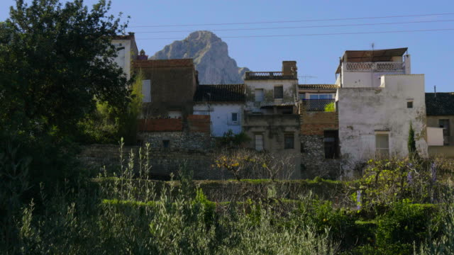 people on cherry tree terraces and back of Benialí village houses with hills