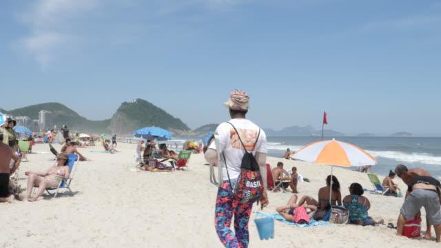 people on copacabana beach on november 27, 2019 in rio de janeiro, brazil - strandurlaub stock-videos und b-roll-filmmaterial