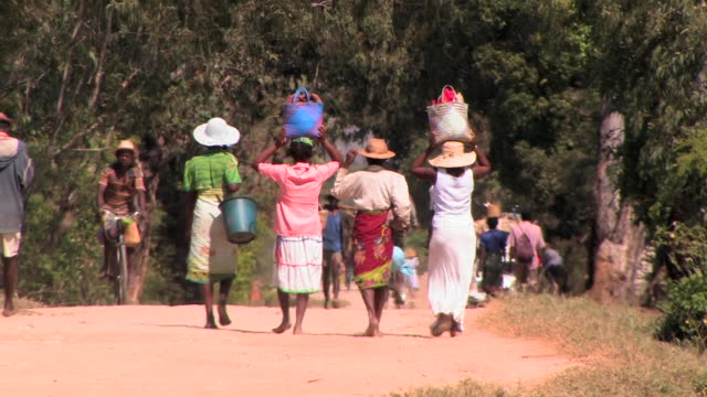 MS, People on dirt road, women carrying bags on heads, rear view, Taolanaro, Toliara Province, Madagascar