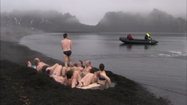 MS, People on geothermal beach, rocky mountains covered with fog in background, Deception Island, Antarctica