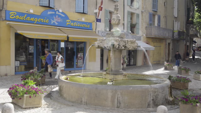 People on marketplace with fountain and bakery in Valensole