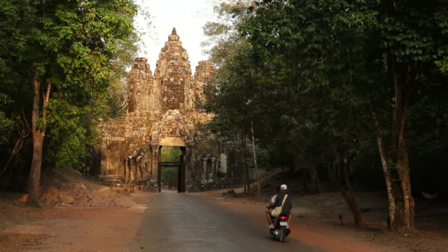 WS People on motorbike at ancient temple / Angkor Wat, Siem Reap, Cambodia