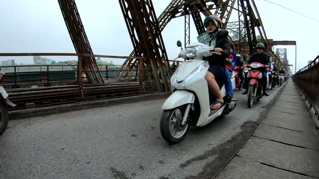 people on motorbikes crossing the long bien bridge - bridge built structure stock videos & royalty-free footage