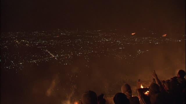 People on mountainside watch Daimonjiyaki, rite of summer in Kyoto