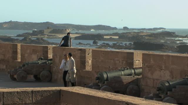 vidéos et rushes de ws people on ramparts of 18th century fort, essaouira, morocco - style du xviiième siècle