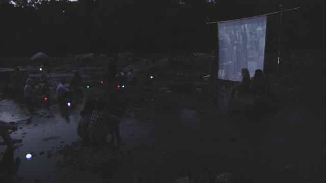 people on river watching movie screen - ニューパルツ点の映像素材/bロール