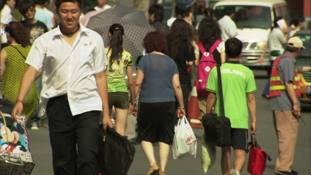 vídeos de stock, filmes e b-roll de ms pan selective focus people on sidewalk in xidan shopping district, beijing, china - plano americano