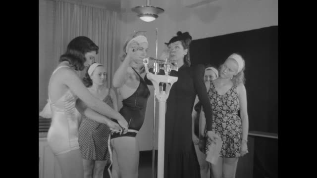 vídeos de stock, filmes e b-roll de people on sidewalk walking by window in richard hudnut building / instructor anne delafield weighing woman in bathing suit on scale and measuring her... - estudante universitária