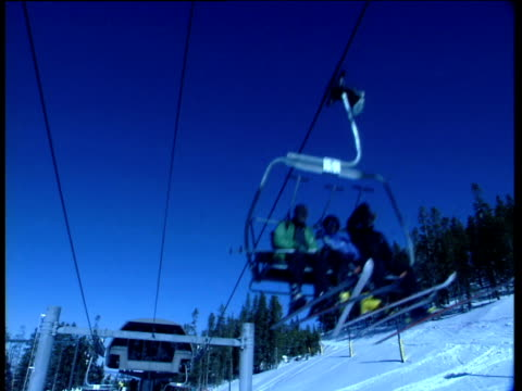 people on ski-lifts wearing ski wear travel over camera. ski slopes fir trees and blue sky in background. winter park colorado blue filter effect - vacanza sulla neve video stock e b–roll