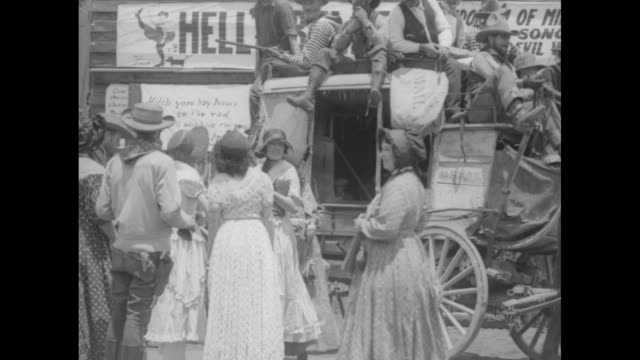 vidéos et rushes de people on stagecoach that pulls up to livery stable with banner over its door that says hell's belles / women and women in old west costumes standing... - animaux au travail