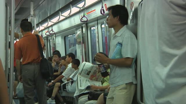 ms people on subway, man drinking soda / beijing, china - bahnreisender stock-videos und b-roll-filmmaterial