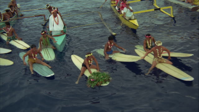 1967 HA WS SHAKY People on surfboards and in catamaran boats throwing flower wreath in water