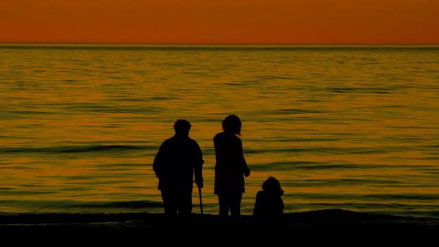 Menschen am Strand bei Sonnenuntergang