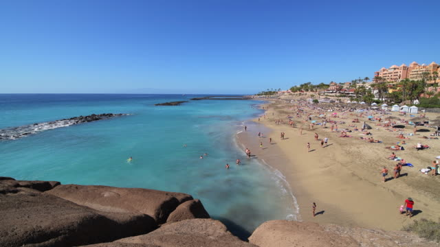 people on the beach playa del duque at costa adeje, tenerife. - atlantic islands stock videos & royalty-free footage