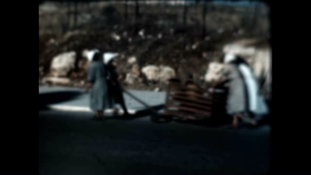 People on the move possibly Palestinian refugees take their belongings in carts From an archival home movie