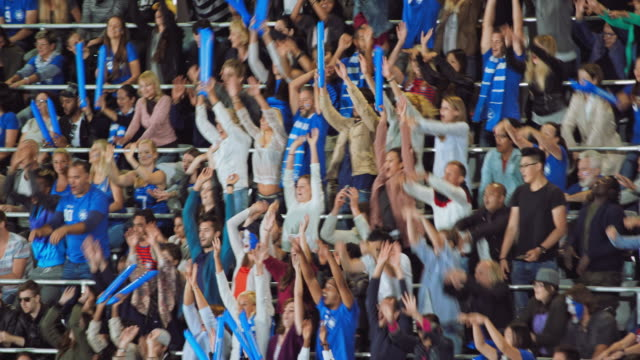 People on the stadium tribune doing the wave