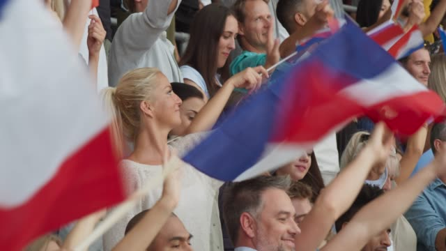 People on the stadium tribune waving French flags