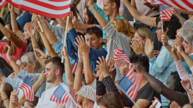 slo mo people on the tribune at the stadium cheering and waving american flags - stars and stripes stock videos & royalty-free footage