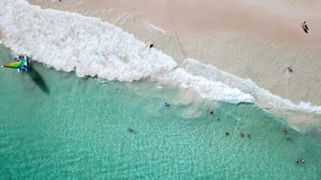 vídeos y material grabado en eventos de stock de people on vacation playing in beautiful turquoise ocean waves on a beach in dominican republic - hispaniola