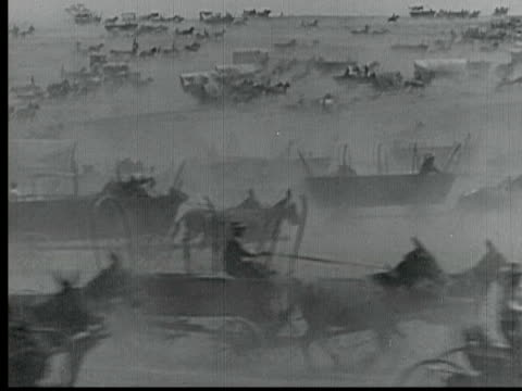 vidéos et rushes de 1925 b/w montage ms ws swish pan la ts pan people on various wagons racing through plains during land rush in 1889, wagon falling down hill / santa clarita, california, usa - ouest américain