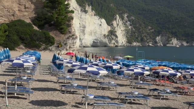 pan / people on vignanotica beach with white limestone rocks at the adriatic sea - deck chair stock videos & royalty-free footage