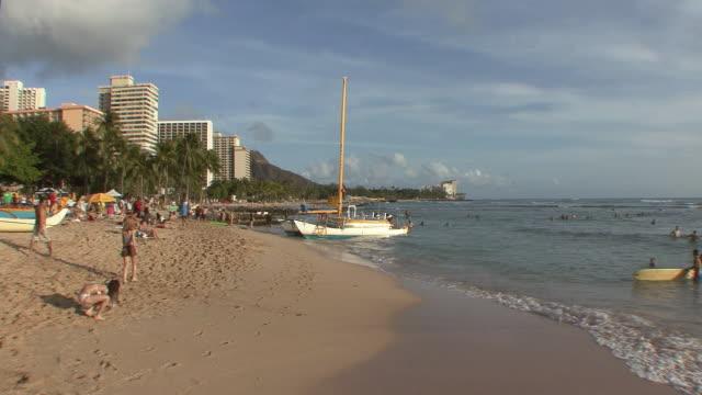 vídeos y material grabado en eventos de stock de ws people on waikiki beach, girl looking for shells in foreground / honolulu, hawaii, usa - honolulu