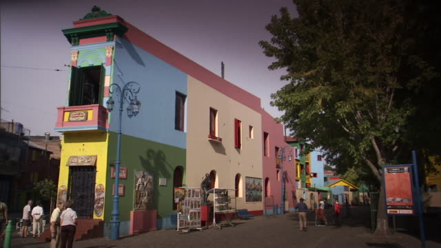 WS People outside brightly colored buildings in La Boca neighborhood/ Buenos Aires, Argentina