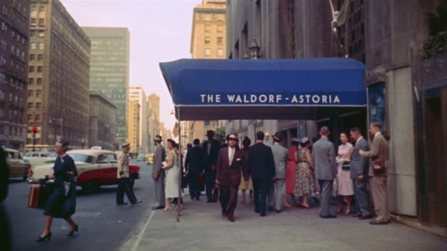 1955 montage people outside waldorf astoria hotel walking, waiting for taxi / traffic on park avenue / new york city - waldorf astoria stock videos & royalty-free footage