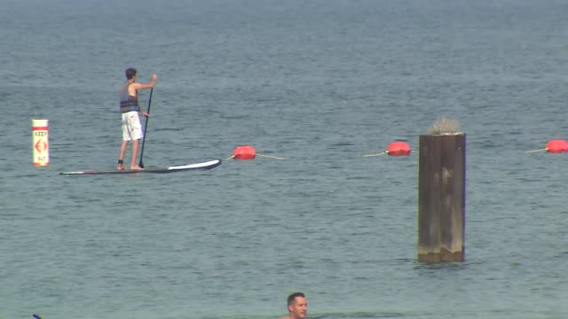 people paddle boarding on lake michigan at north avenue beach on august 27 2013 in chicago illinois - seeufer stock-videos und b-roll-filmmaterial