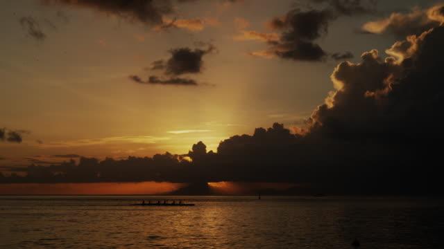 vidéos et rushes de people paddling a canoe on the ocean - île d'huahine