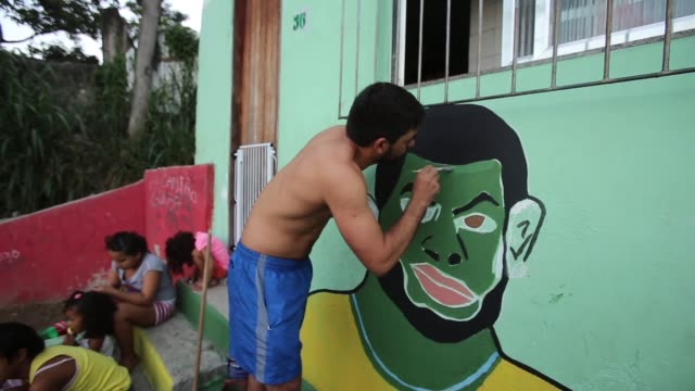 CU People paint Brazilian colors in the Santa Marta favela ahead of the 2014 FIFA World Cup on June 7 2014 in Rio de Janeiro Brazil