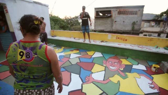 PAN People paint Brazilian colors in the Santa Marta favela ahead of the 2014 FIFA World Cup on June 7 2014 in Rio de Janeiro Brazil