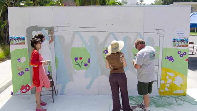 t/l ms people painting a mural outside / los angeles, california, usa - 壁画点の映像素材/bロール