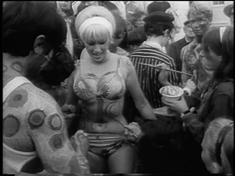 B/W 1967 people painting blonde woman's breasts stomach at bein / Provincetown / newsreel