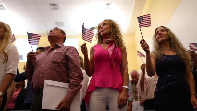 people participate in a ceremony to become american citizens during a us citizenship immigration services naturalization ceremony at the miami field... - citizenship stock videos & royalty-free footage