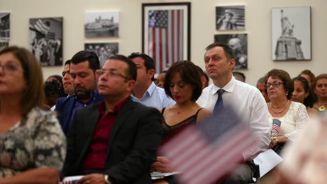 People participate in a ceremony to become American citizens during a US Citizenship Immigration Services naturalization ceremony at the Miami Field...