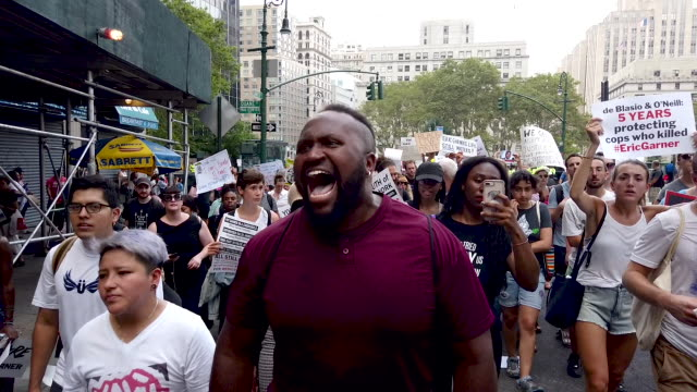stockvideo's en b-roll-footage met people participate in a protest to mark the five year anniversary of the death of eric garner during a confrontation with a police officer in the... - chanten