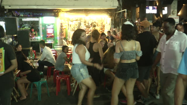 people party on khao san road on the day the government relaxed mourning restrictions. the king of thailand died october 13 and the country is in an... - abbigliamento da neonato video stock e b–roll