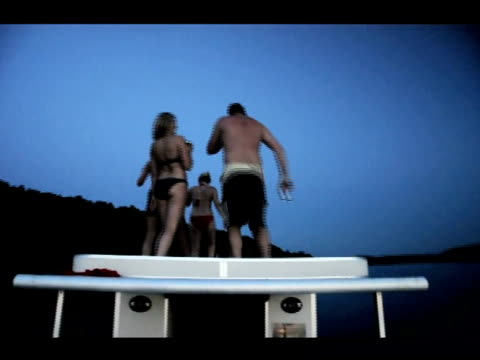/ people partying on boat roof and doing the cupid shuffle dance / woman slips and falls into the water as her friends peer over edge dancing woman... - wipeout stock videos & royalty-free footage