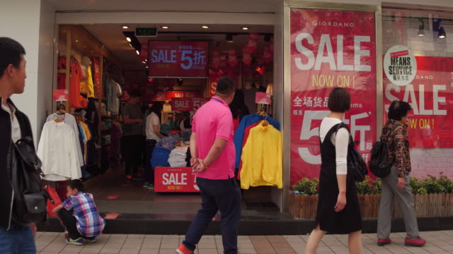 People pass a clothing store in famous Wangfujing Street on May 4 2017 in Beijing China Wangfujing is a main business street for tourism next to the...