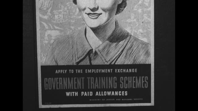 """people pass a large banner, """"train to win - government training schemes"""" / vs posters of a smiling man in a cap: """"train to win"""" and a woman """"apply to... - 製図板点の映像素材/bロール"""