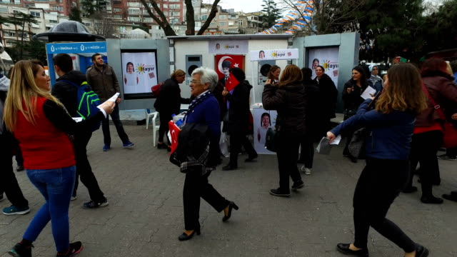 """people pass a stall handing out leaflets supporting the """"no"""" vote at a campaign stall in uskudar on march 8, 2017 in istanbul, turkey. turkey will... - brochure stock videos & royalty-free footage"""