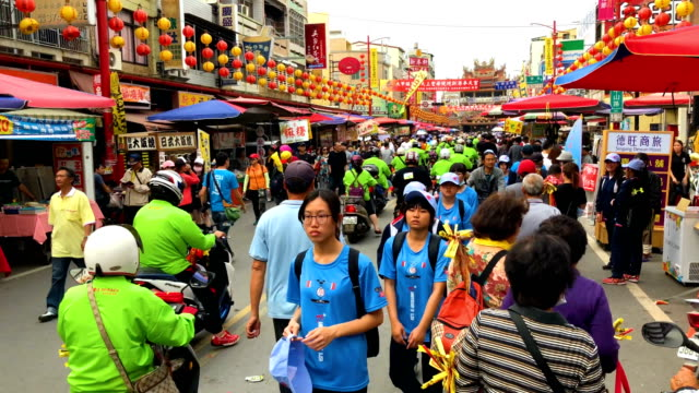 people pass along a street market while festivities take place to mark the attendance of a statue of mazu at the nearby xingang fengtian temple on... - 台湾点の映像素材/bロール