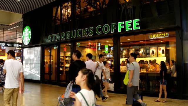 vídeos de stock, filmes e b-roll de people pass by starbucks coffee at beijing south railway station on july 2 2017 in beijing china - starbucks