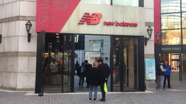 People pass by the New Balance store at Solana shopping mall on Feb 12 2017 in Beijing China