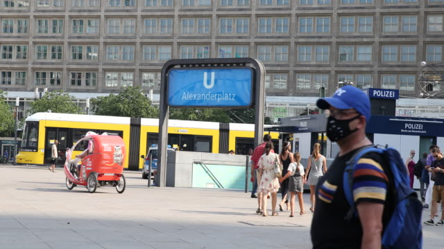 people pass by wearing protective face masks at alexanderplatz at temperatures above 30 degrees during the novel coronavirus pandemic on august 07,... - アレクサンダープラッツ点の映像素材/bロール